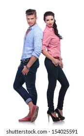 full length photo of a young casual couple standing back to back and looking into the camera. on white background