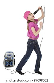 Full length photo of young girl singing into microphone with karaoke machine in background, isolated on white.
