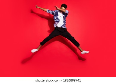 Full length photo of young handsome black man jump up pose dab active isolated over red color background