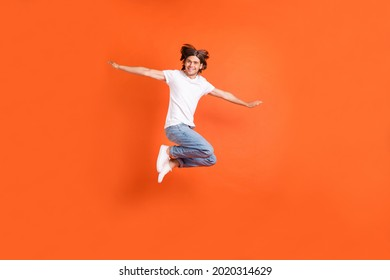 Full length photo of young happy funky man jump up air hands wings plane smile isolated on orange color background