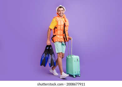 Full length photo of young man happy positive smile go walk trip abroad lifesaving vest flippers isolated over violet color background