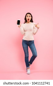 Full length photo of young woman 20s wearing jeans advertising smartphone with pointing finger isolated over pink background
