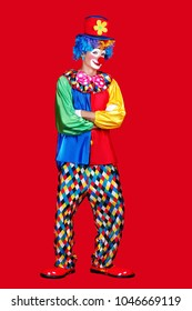 Full length picture of a standing clown in a hat and giant clown boots against red background
