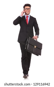 full length picture of a young business man walking forward with a briefcase in one of his hands and talking at the phone while looking away from the camera on white background