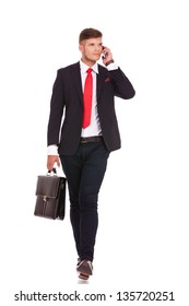 full length picture of a young business man holding a briefcase and walking forward while speaking on the phone and looking away from the camera. isolated on white background