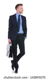 full length picture of a young business man holding a briefcase in a hand and the other in his pocket while looking to his side, away from the camera. on white background