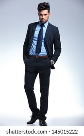 full length picture of a young business man looking at the camera while holding both hands in his pockets. on a gray background