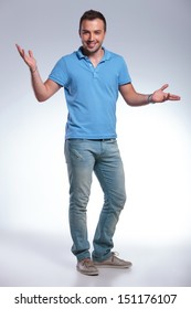 full length picture of a young casual man welcoming everyone with his arms wide open and a big smile. on gray background