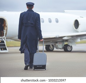 Full length pilot going to aircraft while keeping baggage in hand. Work concept