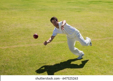 Full length of player catching ball on field during sunny day