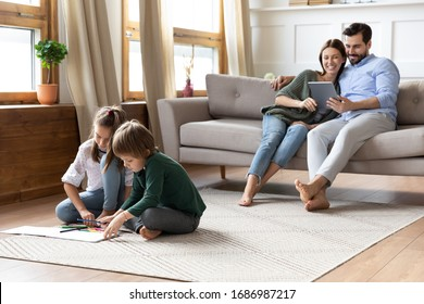 Full length playful little children siblings sitting on floor carpet drawing pictures while addicted to technology smiling parents resting on couch with computer tablet, family weekend pastime.