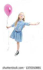 Full length. Playful little girl holding pink balloon. Isolated on white background.