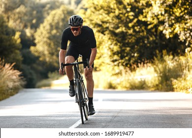 Full length portrait of active man in sport clothing and protective helmet riding bike with blur background of summer nature. Concept of workout and races.