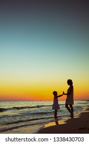 Full length portrait of active mother and daughter tourists on the ocean coast at sunset having fun time.