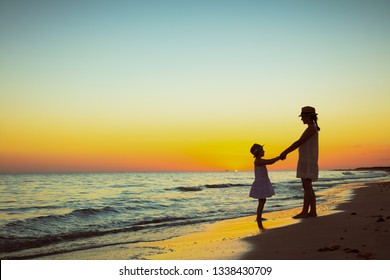 Full length portrait of active mother and daughter on the ocean shore at sunset having fun time.
