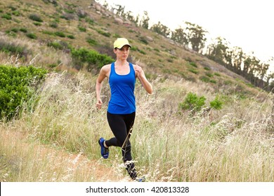 Full length portrait of active older woman running in nature
