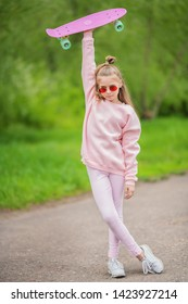 A full length portrait of an active teenager girl posing on the road with a skateboard. Casual kids fashion, active lifestyle.