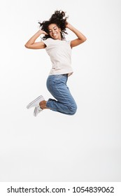 Full length portrait of adorable american woman with afro hairstyle wearing jeans and t-shirt jumping and rejoicing with perfect smile isolated over white background