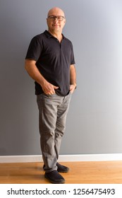 Full length portrait of adult middle-aged bold man in glasses, wearing black polo and grey jeans, standing in half turn with his fingers in pockets and looking at camera