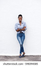 Full length portrait of african american woman smiling against white wall