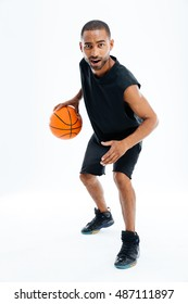 Full length portrait of an african man playing basketball isolated on a white background