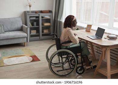 Porträt afroamerikanischer Frau im Rollstuhl, die per Videochat anruft, während sie am Schreibtisch mit einem Laptop in minimalgrauem Innenraum sitzt, Kopienraum