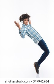 Full length portrait of afro american man with headphones dancing isolated on a white background