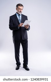 Full length portrait of aged businessman wearing suit and tie. Businessman in years standing on white background. Boss using tablet computer