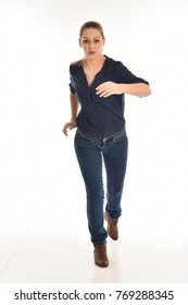 full length portrait of air wearing blue shirt and denim pants, standing pose on white background.