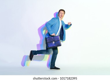 Full length portrait of amazed male hurrying to job. He holding suitcase. Late for labor concept