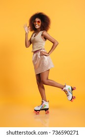 Full length portrait of a amusing afro american woman dressed in retro clothes and wearing skates while standing and showing ok gesture isolated over yellow background
