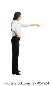 full length portrait of angry screaming woman in formal wear pointing finger at something. isolated on white background
