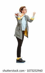 Full length portrait of angry, violent, enraged female student in glasses holding books isolated on white background. Female figure of caucasian model at studio.