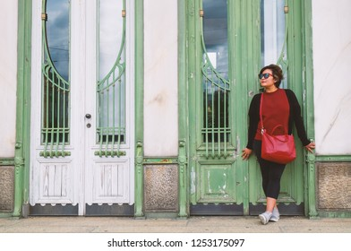 Full length portrait of an Asian woman in red blouse and red cross body bag standing in front of white and green wooden door in vintage style.