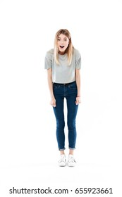 Full length portrait of an astonished cute girl standing with mouth opened isolated over white background