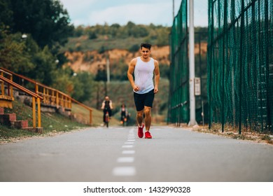 Full length portrait of an athletic young man running and working out in the park