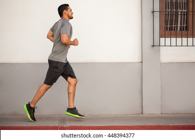 Full length portrait of an athletic young man running and working out in the city
