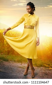 Full length portrait of attractive african american girl standing in vineyard at sunset. Young woman in stylish yellow dress with eyes closed.