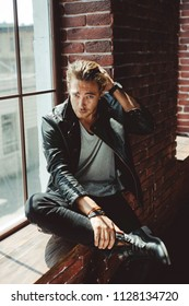 Full length portrait of an attractive man with fair hair wearing stylish leather jacket and jeans sitting on a window sill on a brick wall background on a sunny day, looking at camera.Texture effect.