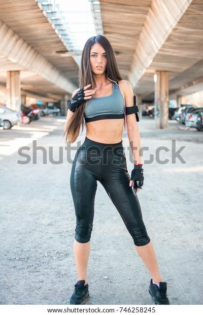 Full length portrait of attractive sportswoman standing under the bridge.