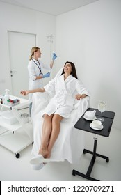 Full length portrait of attractive woman in white bathrobe lying on deckchair during medical procedure. Physician checking IV infusion