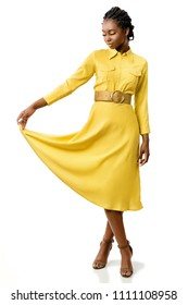 Full length portrait of attractive young african american girl in stylish yellow dress. Elegant woman holding end of dress with eyes closed.Isolated on white background.
