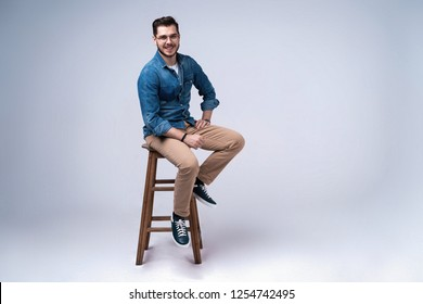 Full length portrait of an attractive young man in jeans shirt sitting on the chair over grey background