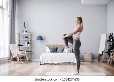 Full length portrait of attractive young woman working out at home, doing pilates exercise on mat. Training indoor.