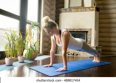 Full length portrait of attractive young woman working out at home in living room, doing yoga or pilates exercise on blue mat, standing in plank pose (phalankasana)