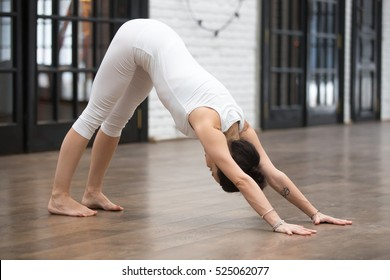 Full length portrait of attractive young woman working out in luxury fitness center, doing yoga or pilates exercise without mat on wooden floor. Downward facing dog, adho mukha svanasana pose