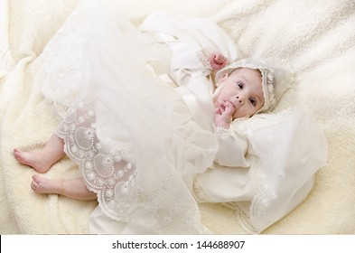 Full length portrait of baby with christening clothes.