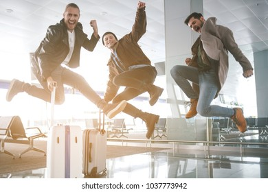 Full length portrait of beaming comrades jumping in hall. Baggages locating opposite them. Fun and journey concept