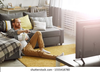 Full length portrait of bearded man switching channels while watching TV at home in bachelors pad, copy space