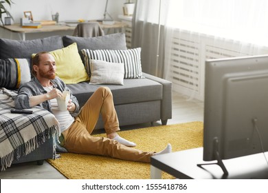 Full length portrait of bearded man eating takeout noodles while watching TV at home in bachelors pad, copy space